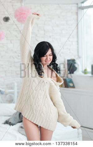 Happy women in white sweater awake in bedroom. Laughing in bedroom beautiful brunette in morning. Satisfied girl in white pullover stretching herself
