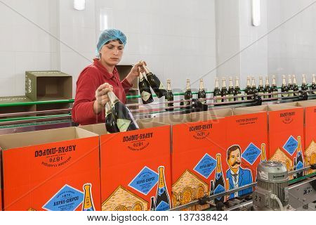 ABRAU-DURSO, RUSSIA - MAY 14, 2016: The winery Abrau-Durso. Worker puts bottles of sparkling wine in boxes.  Abrau-Durso is Russia's oldest sparkling wine producer