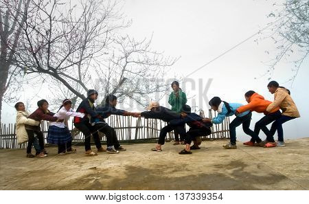LAO CAI, VIETNAM, February 9, 2016 student groups, ethnic Hmong, Lao Cai highland playing tug of war, in the morning fog