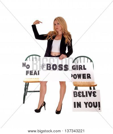 A lovely woman in a black jacket standing with empowerment sign's pointing her finger at herself isolated for white background.