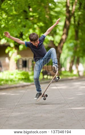 Little skateboarder balancing in mid-air with skateboard