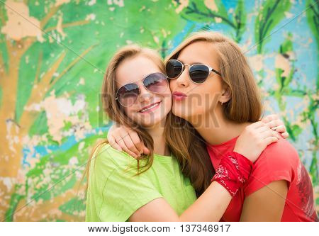 Bright stylish lifestyle urban portrait of two pretty best friends girls. Having fun kiss and say hello. Two funny affectionate women friends laughing and kissing outdoors.