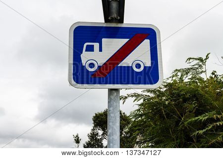 Blue sign showing lorry or HGV with red line through it to warn that the road is unsuitable for lorries.