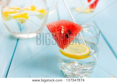 Fresh water with lemon and melon on blue wood table