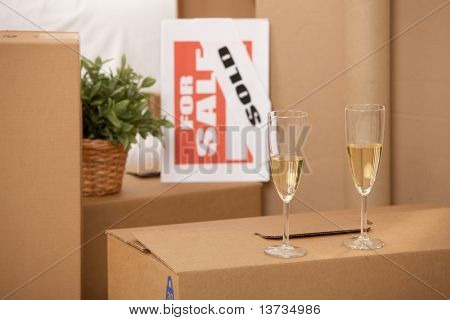 Celebration of new home, two champagne glasses standing on pile of boxes with for sale sign.?