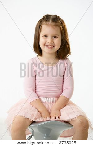 Portrait of happy little girl wearing ballet costume sitting on high chair against white background, looking at camera, smiling.?