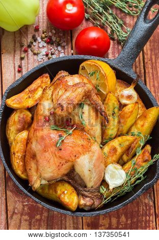 Baked chicken with potatoes garlic lemon and thyme. A delicious dinner in the rustic style. Selective focus. Top view