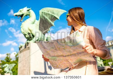 Young female traveler making selfie with smart phone with Dragon statue on the bridge in Ljubljana city. Dragon statue is one of the most famous symbols of the capital of Slovenia
