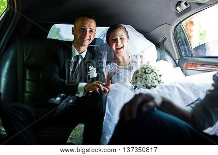 happy wedding couple sitting in limo at wedding day