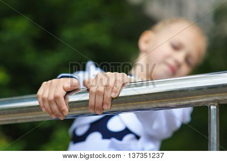 Portrait of a little girl. Child in a beautiful dress looking to side hands on railing. Green tree in background. focus on hands.