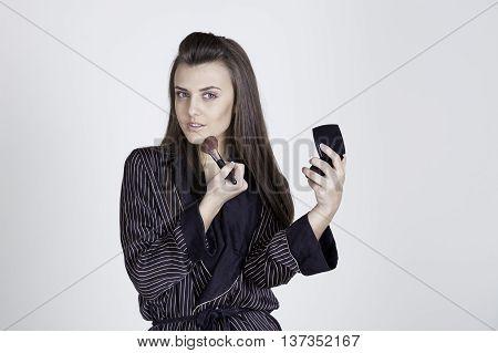 beautiful girl makes herself makeup brush cosmetics