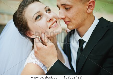 Close Up Portrait Of Groom Holding Hand On Face Bride