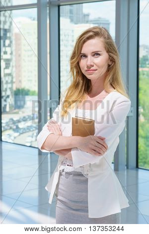 Beautiful businesswoman portrait with copybook in her hands.