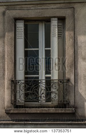 Old granite building with window and metal shutters upper floor Paris France