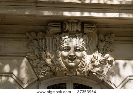 Face carved as part of arch above doorway old.