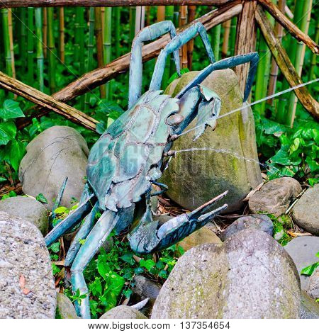 metal sculpture crabs partially oxidized sprays water to passers-by a forest of bamboo canes