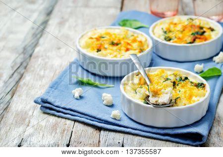 Chicken Spinach Cauliflower casserole on white wood background.