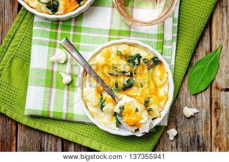 Chicken Spinach Cauliflower casserole on a dark wood background.