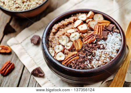 Chocolate Quinoa breakfast bowl decorated with hazelnuts Pecan chocolate and coconut.