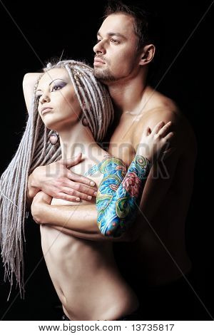 Shot of a passionate loving couple. Over black background.