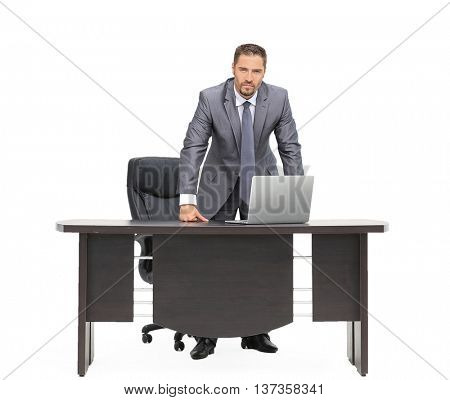 Serious businessman standing next to the table isolated on white background