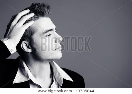 Young man dressed in rock'n'roll style, posing over blue background.