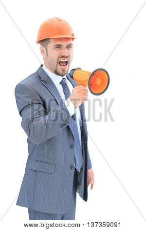 Portrait of young angry architect  shouting using megaphone over white background