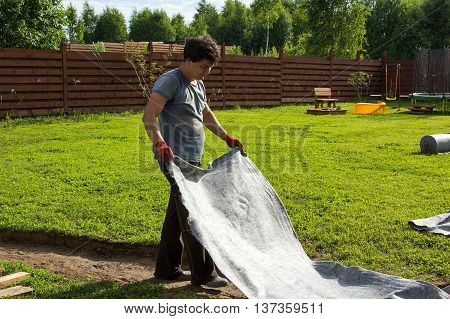 Man Lay Geotextiles In Pit For Garden Path