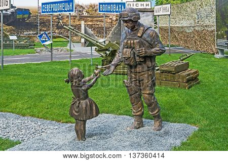 Dnepropetrovsk Ukraine - May 19 2016: Open air museum dedicated to war in the Donbass. Little girl has treated apple Ukrainian soldier