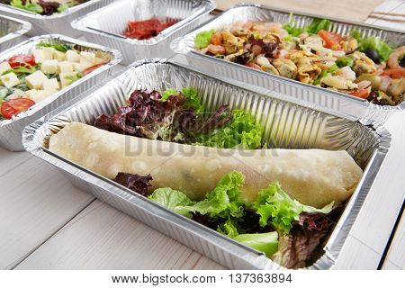 Healthy eating, diet concept. Take away organic food. Weight loss nutrition in foil boxes. French crepe roll with vegetable filling and lettuce at white wood