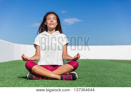 Yoga fitness woman doing summer meditation outdoor. Happy asian athlete meditating before strength training workout sitting in lotus position on outside grass gym floor. Active living.