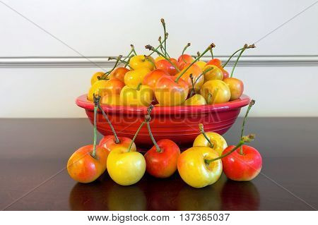 Pile of Rainier Cherries in a red bowl and on a wooden table closeup