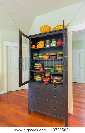 Cupboard with colorful stoneware dinnerware in home with cherry hardwood floor