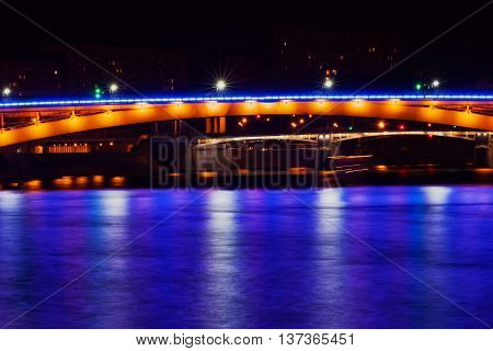 View of bridge with bright blue light reflection on water surface at night time. Art effect light blur.