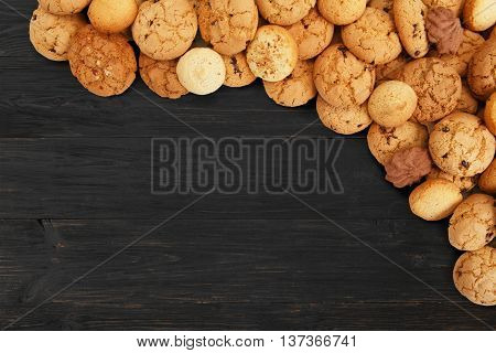 Cookies background. Sweet chocolate chips biscuits heap at black wood background with copy space. Oatmeal, chocolated drops and other sweets. Fattening dessert for tea on wooden table top view