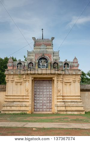 Chettinad India - October 18 2013: Entrance to Nagar Soorakudi Sundesaswar Meenakshi Ambal Temple. Yellow wall and gate decorated with statues.