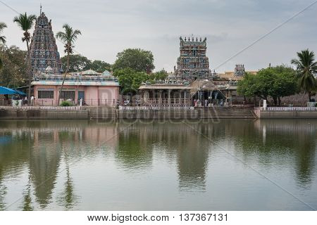 Tamil Nadu India - October 18 2013: Pillayarpatti Karpaga Vinayagar temple seen from the other side of the temple pond. Gray-blue sky green trees envelope the Gopurams and entrance buildings.