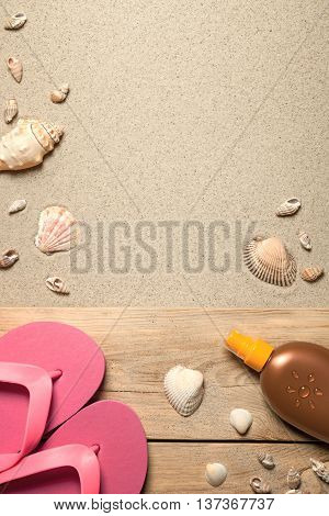 Summer concept with pink flip flops shells and suntan oil on sandy beach