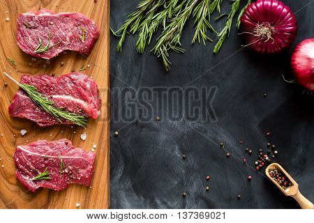 fresh meat on chopping board with rosemary, red onion, pepper. Raw meat. three peece of beef ready for cooking on wooden board on black background . close up. top view. place for text