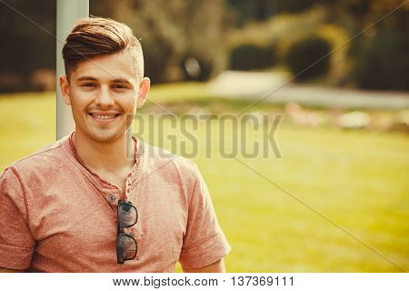 Handsome masculinity relax concept. Smiling boy enjoying park. Young relaxed man outdoors.