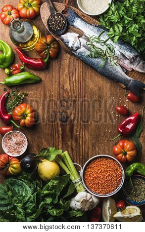 Raw uncooked seabass fish with vegetables, grains, herbs, spices and olive oil on rustic wooden chopping board with copy space in the center, top view, vertical copmosition