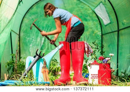 Gardening tools outdoor in garden red rubber boots water can hose. Woman farmer working in greenhouse in the background