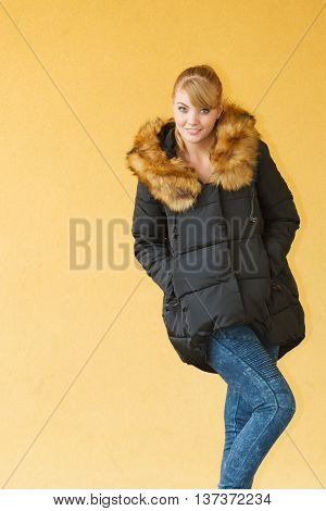 Beautiful smiling attractive fashionable girl wearing black warm jacket on orange brown wall background. Fashion in winter time.