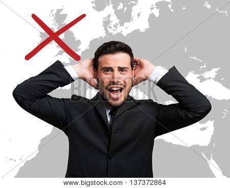 Desperate businessman in front of a world map with the united kingdom erased