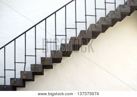 The photograph of an old staircase with a rusty railing and zig zag steps.