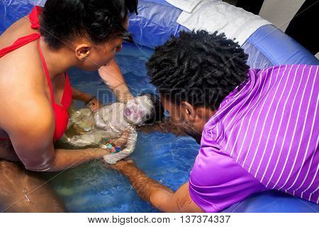 An African American couple delivers their newborn baby in a pool of water at home during a homebirth with help from their midwife.