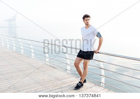 Attractive young man athlete with armband and cell phone standing on pier