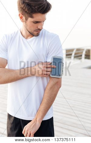 Concentrated young sportsman using smartphone in armband outdoors