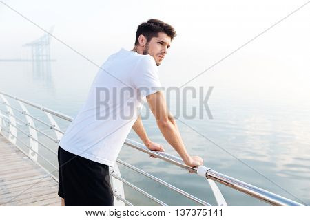 Serious young sportsman standing on pier and looking at the sea