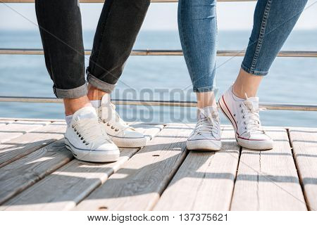 Young couple in love standing at the seaside in gumshoes
